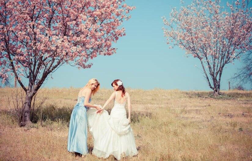 Wenn die beste Freundin heiratet: Braut und Trauzeugin auf einem Feld mit Kirschbäumen