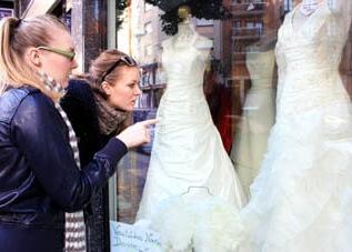 Wenn die beste Freundin heiratet: Braut und Trauzeugin sehen sich Brautkleider im Schaufenster an