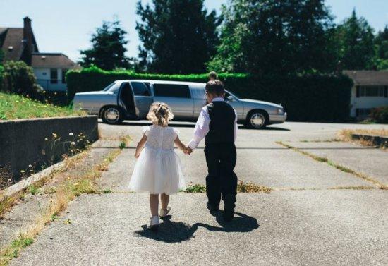 zwei kinder in festlicher kleidung laufen auf ein auto zu