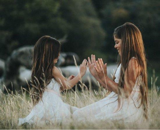 zwei mädchen auf der hochzeit sitzen im gras